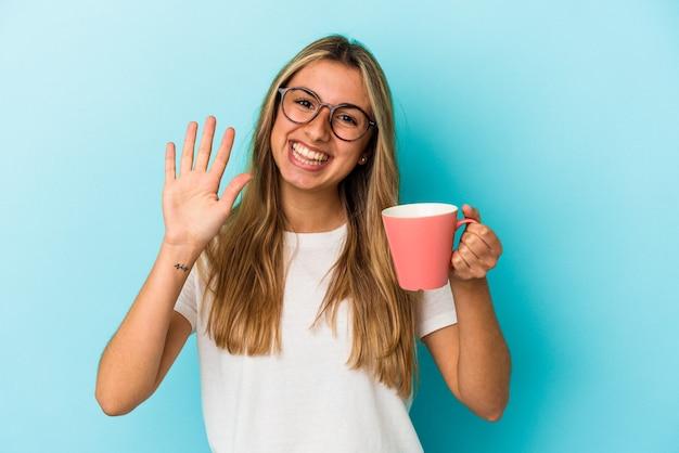 Junge kaukasische blonde frau, die einen becher lokalisiert an der blauen wand hält, die fröhlich lächelnd zeigt nummer fünf mit den fingern