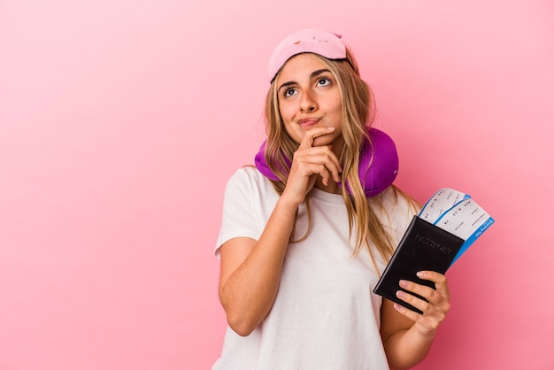Junge kaukasische blonde frau, die einen pass und fahrkarten hält, lokalisiert auf rosa hintergrund, der seitwärts mit zweifelhaftem und skeptischem ausdruck schaut.