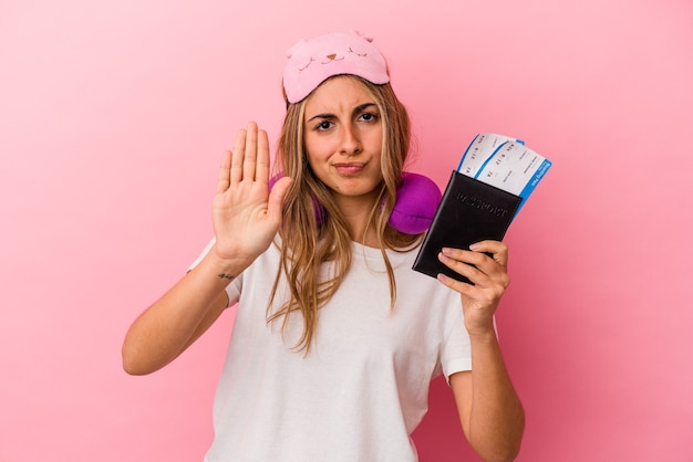 Junge kaukasische blonde frau, die einen pass und tickets hält, um lokalisiert auf rosa hintergrund zu stehen, der mit ausgestreckter hand steht, die stoppschild zeigt, das sie verhindert.