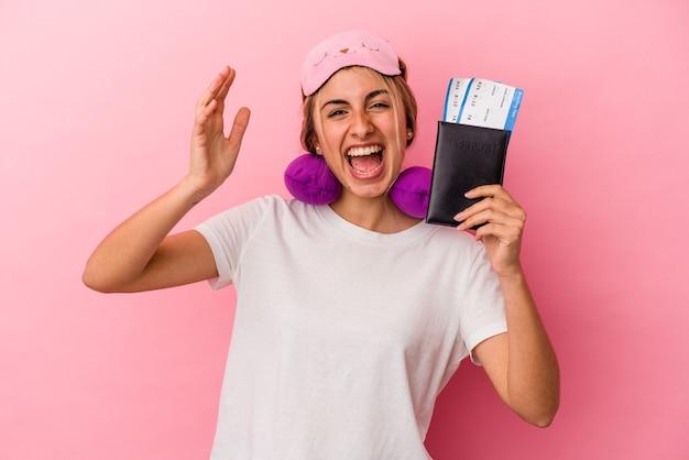 Junge kaukasische blonde frau, die einen reisepass und reisetickets einzeln auf rosafarbenem hintergrund hält und eine angenehme überraschung empfängt, aufgeregt und die hände hebt.