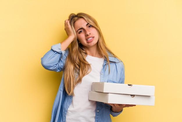 Junge kaukasische blonde frau, die pizzas einzeln auf gelbem hintergrund hält, ist schockiert, sie hat sich an ein wichtiges treffen erinnert.