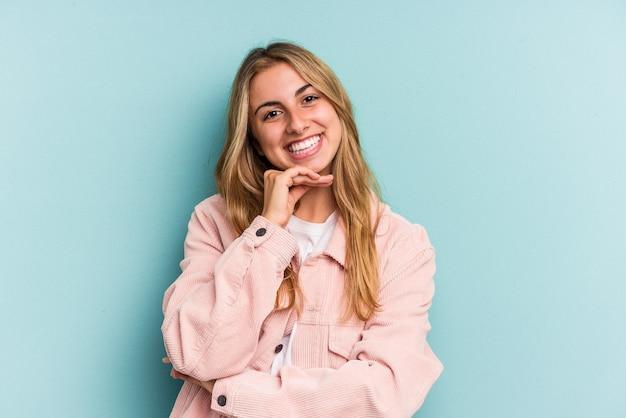 Junge kaukasische blonde frau isoliert auf blauem hintergrund lächelt glücklich und selbstbewusst und berührt das kinn mit der hand.