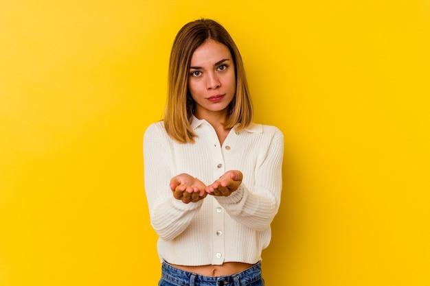 Junge kaukasische dünne frau lokalisiert auf gelbem hintergrund, der etwas mit palmen hält, der kamera anbietet.