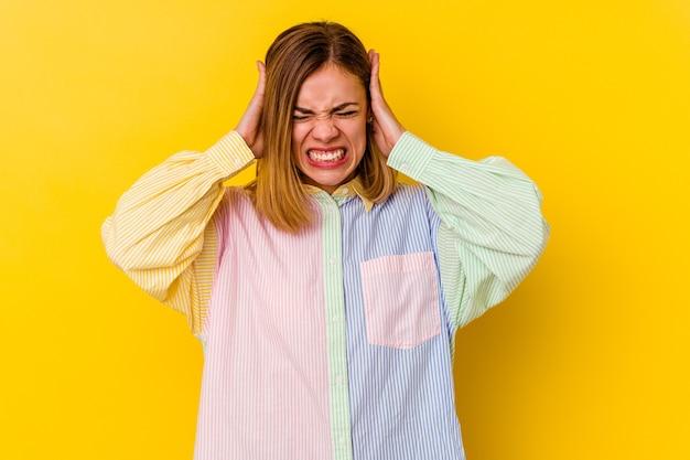 Junge kaukasische dünne frau lokalisiert auf gelbem hintergrund, der ohren mit händen bedeckt, die versuchen, nicht zu lautes geräusch zu hören.