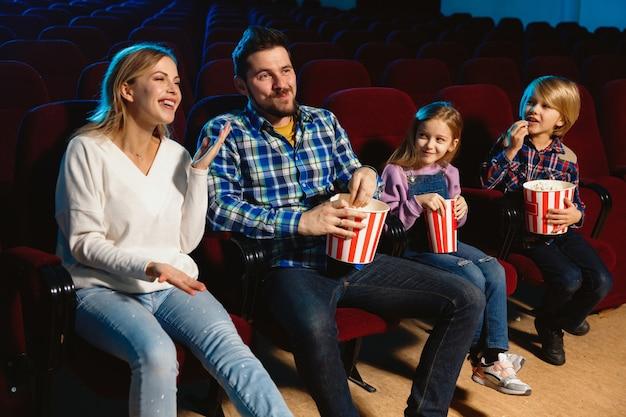 Junge kaukasische familie, die einen film in einem kino, haus oder kino sieht. sieh ausdrucksstark, erstaunt und emotional aus. allein sitzen und spaß haben. beziehung, liebe, familie, kindheit, wochenendzeit.