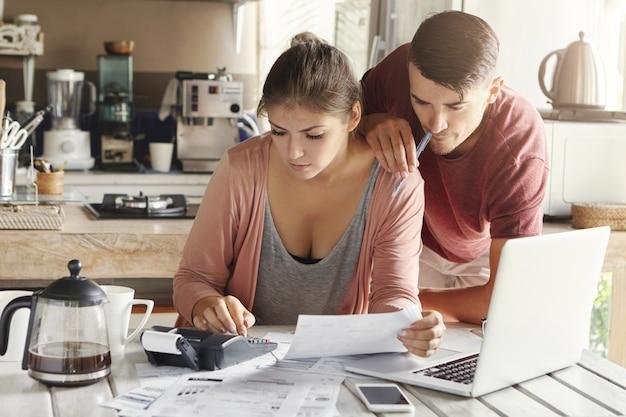 Junge kaukasische familie vor kreditschuldenproblem. schöne frau, die ein stück papier hält und finanzen berechnet