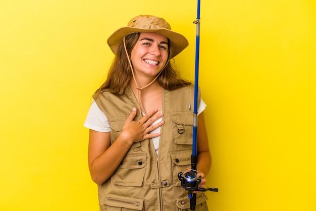 Junge kaukasische fischerin, die eine auf gelbem hintergrund isolierte stange hält, lacht laut und hält die hand auf der brust.