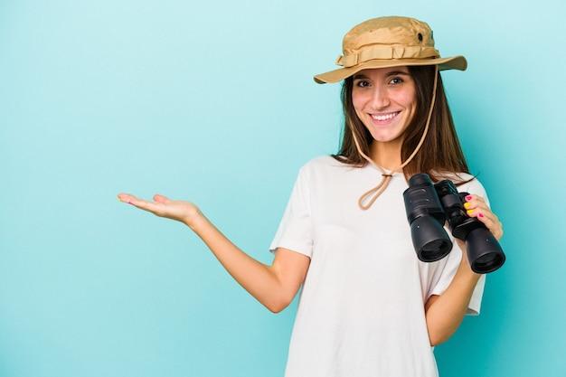 Junge kaukasische forscherin, die ein fernglas auf blauem hintergrund hält, das einen kopienraum auf einer handfläche zeigt und eine andere hand an der taille hält.