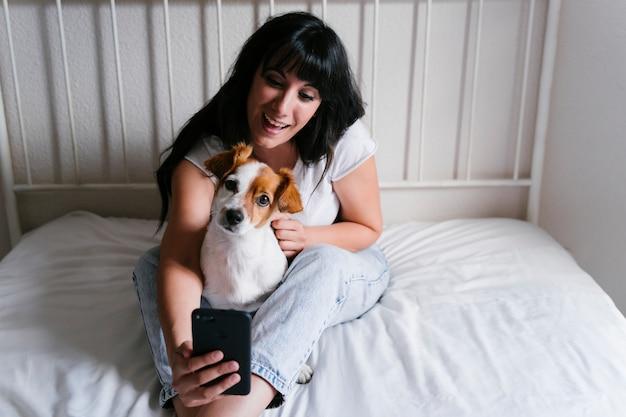 Junge kaukasische frau auf bett, die ein selfie mit handy mit ihrem niedlichen kleinen hund nimmt.