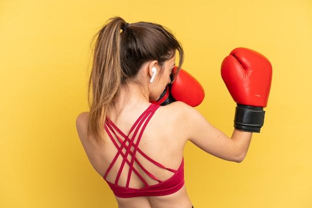 Junge kaukasische frau auf blauem hintergrund mit boxhandschuhen isoliert
