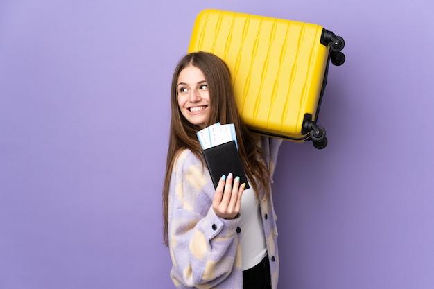 Junge kaukasische frau auf lila wand im urlaub mit koffer und pass