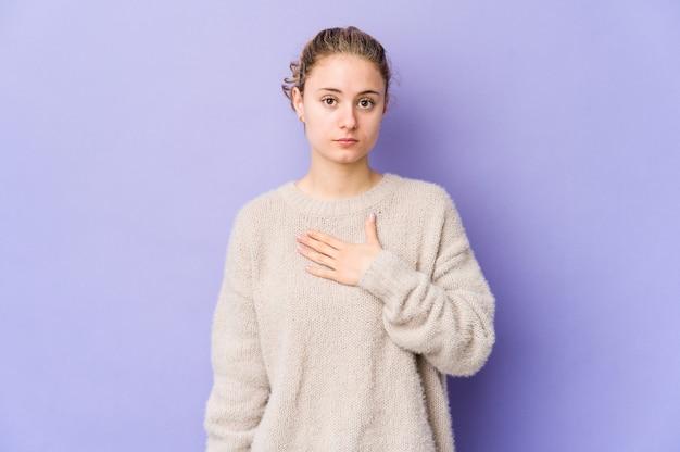 Junge kaukasische frau auf purpur, die einen eid leistet und hand auf brust legt.