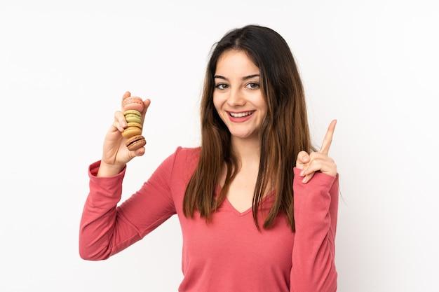 Junge kaukasische frau auf rosa wand, die bunte französische macarons hält und eine große idee aufzeigt