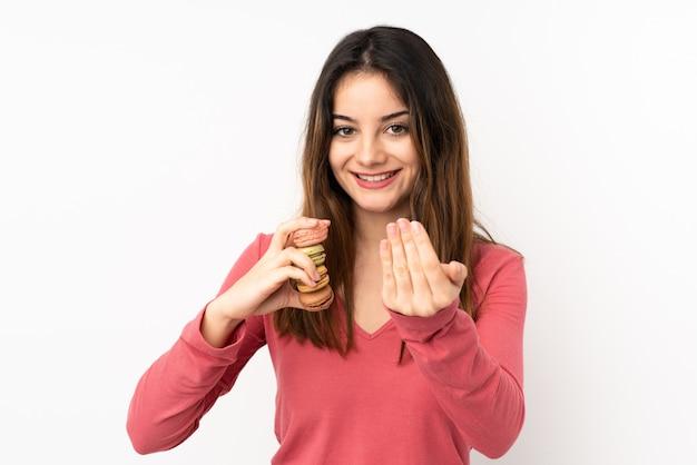 Junge kaukasische frau auf rosa wand, die bunte französische macarons hält und einlädt, zu kommen