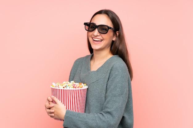 Junge kaukasische frau auf rosa wand mit 3d brille und hält einen großen eimer popcorn