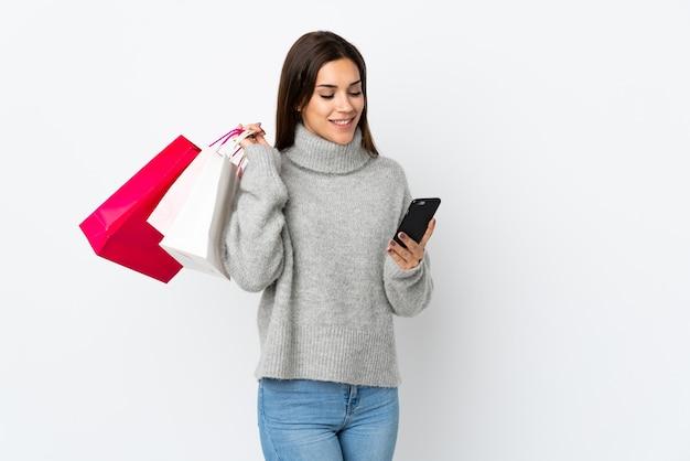Junge kaukasische frau auf weiß, die einkaufstaschen hält und eine nachricht mit ihrem handy an einen freund schreibt