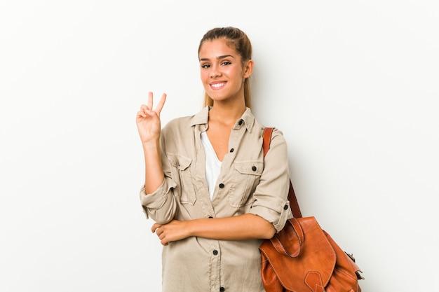 Junge kaukasische frau bereit zu einer reise, die nummer zwei mit den fingern zeigt.