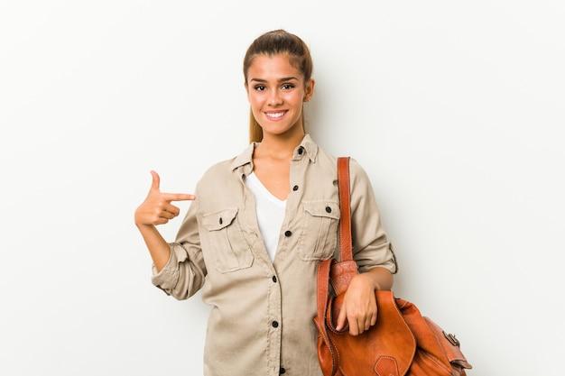 Junge kaukasische frau bereit zu einer reiseperson, die eigenhändig auf einen hemdkopienraum, stolz und überzeugt zeigt