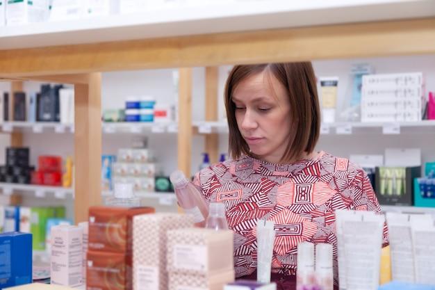 Junge kaukasische frau brunette wählt hautpflegeprodukte auf dem einkaufen