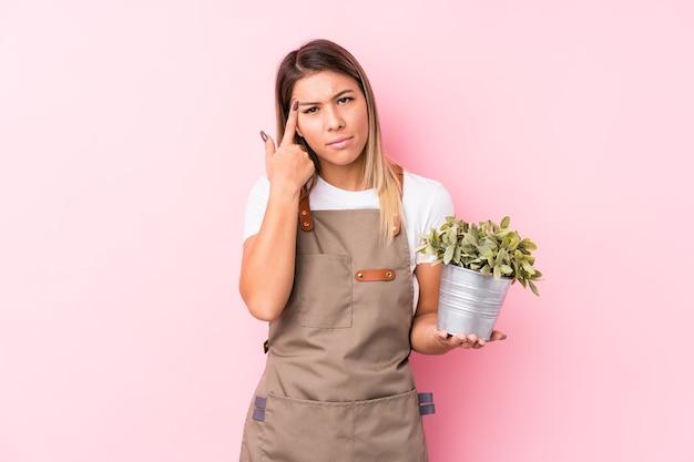 Junge kaukasische frau des gärtners isoliert, die eine enttäuschungsgeste mit zeigefinger zeigt.