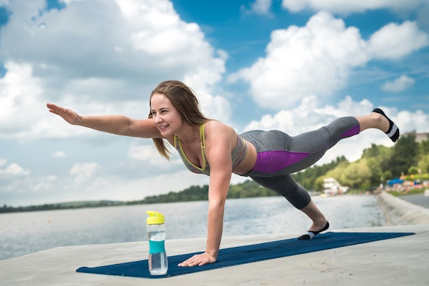 Junge kaukasische frau, die aktive trainingsübung auf einer yogamatte nahe dem fluss im sommer tut