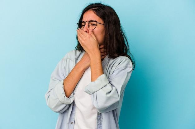 Junge kaukasische frau, die auf blauem hintergrund isoliert ist, leidet an halsschmerzen aufgrund eines virus oder einer infektion.