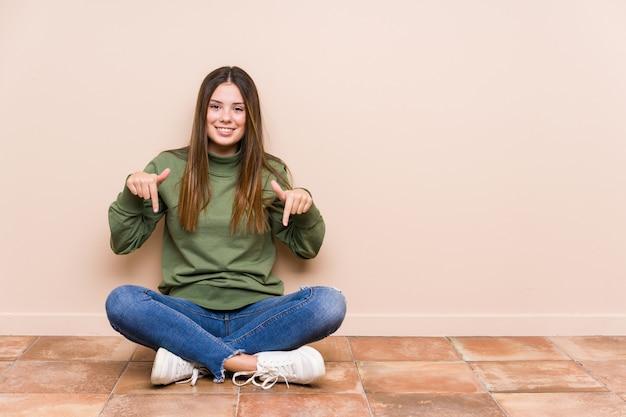 Junge kaukasische frau, die auf dem boden sitzt, zeigt mit den fingern nach unten