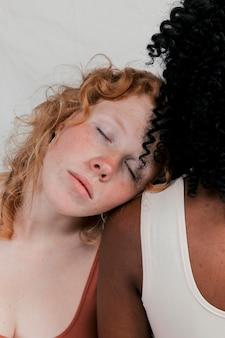 Junge kaukasische frau, die auf dunkelhäutiger freundin über ihrer schulter schläft
