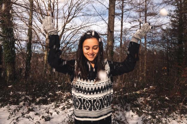 Junge kaukasische frau, die auf einem schneebedeckten wald spielt.