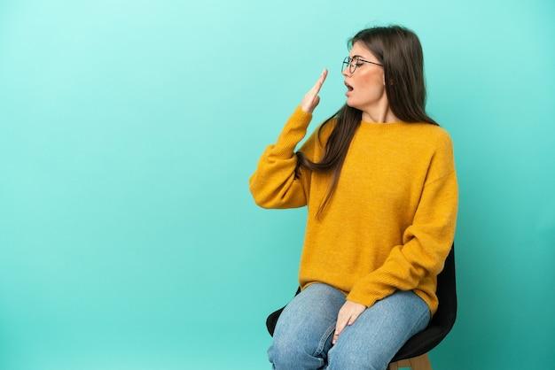 Junge kaukasische frau, die auf einem stuhl sitzt, der auf blauem hintergrund lokalisiert wird, gähnt und weit geöffneten mund mit der hand bedeckt