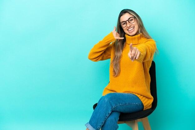 Junge kaukasische frau, die auf einem stuhl sitzt, der auf blauem hintergrund lokalisiert wird, telefongeste macht und nach vorne zeigt