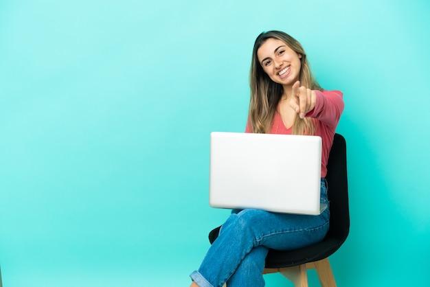 Junge kaukasische frau, die auf einem stuhl sitzt, mit ihrem pc auf blauem hintergrund isoliert, zeigt mit einem selbstbewussten ausdruck mit dem finger auf sie