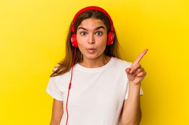 Junge kaukasische frau, die auf gelbem hintergrund musik hört, die eine großartige idee hat, konzept der kreativität.