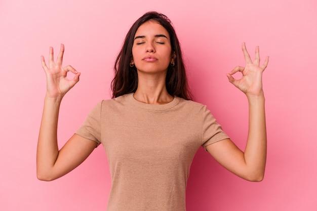 Junge kaukasische frau, die auf rosafarbenem hintergrund isoliert ist, entspannt sich nach einem harten arbeitstag, sie macht yoga.