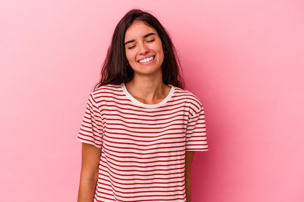 Junge kaukasische frau, die auf rosafarbenem hintergrund isoliert ist, lacht und schließt die augen, fühlt sich entspannt und glücklich.