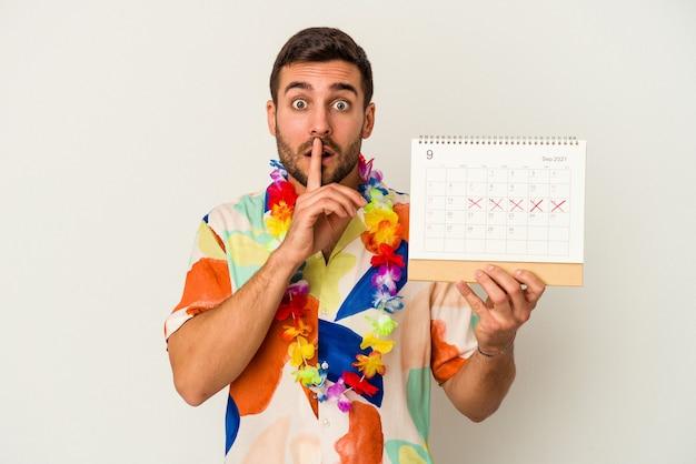 Junge kaukasische frau, die auf seine ferien wartet, die einen kalender halten, der auf weißer wand lokalisiert wird, ein geheimnis hält oder um stille bittet.