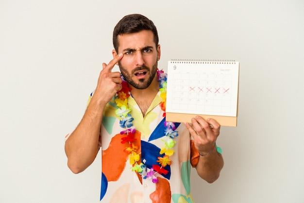 Junge kaukasische frau, die auf seine ferien wartet, die einen kalender lokalisiert auf weißer wand halten, die eine enttäuschungsgeste mit zeigefinger zeigt