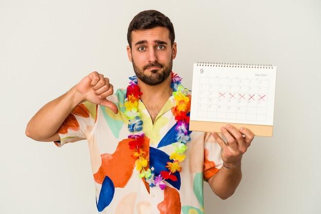 Junge kaukasische frau, die auf seine ferien wartet, hält einen kalender lokalisiert auf weißer wand, die eine abneigungsgeste zeigt, daumen nach unten