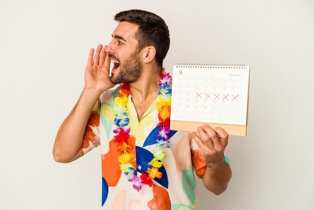 Junge kaukasische frau, die auf seine ferien wartet, hält einen kalender lokalisiert auf weißer wand, die schreit und handfläche nahe geöffnetem mund hält
