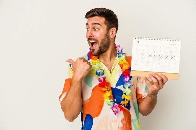 Junge kaukasische frau, die auf seinen urlaub wartet und einen kalender hält, der auf weißem hintergrund lokalisiert wird, zeigt mit dem daumenfinger weg, lacht und sorglos