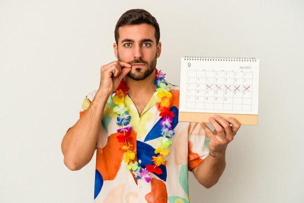Junge kaukasische frau, die auf seinen urlaub wartet und einen kalender hält, der auf weißem hintergrund mit fingern auf den lippen lokalisiert wird, die ein geheimnis halten.