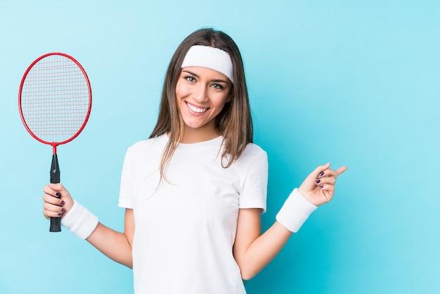 Junge kaukasische frau, die badminton spielt, isoliert lächelnd und beiseite zeigend, etwas an der leeren stelle zeigend.