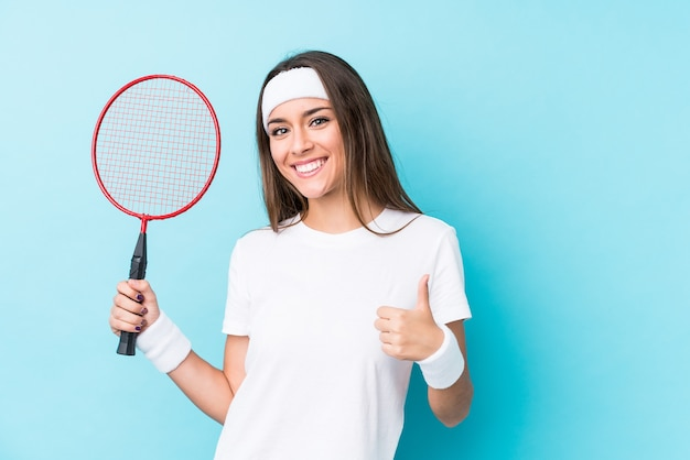 Junge kaukasische frau, die badminton spielt, isoliert lächelnd und daumen hochhebend