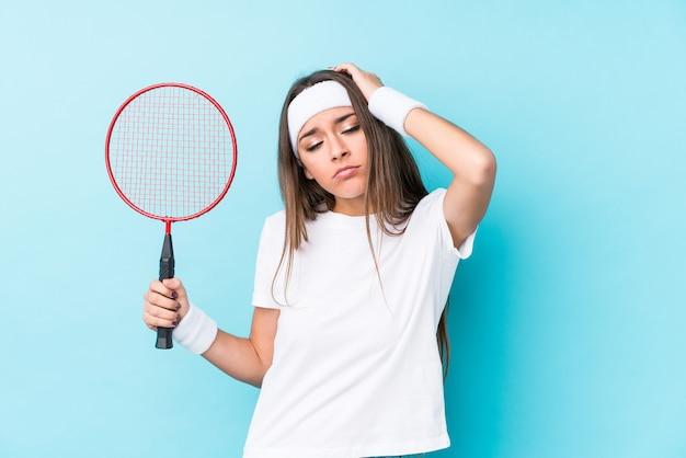 Junge kaukasische frau, die badminton spielt, isoliert, schockiert, sie hat sich an wichtiges treffen erinnert.