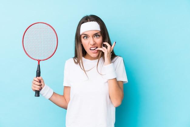Junge kaukasische frau, die badminton spielt, isolierte beißende fingernägel, nervös und sehr ängstlich.
