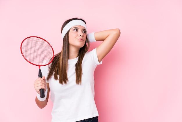 Junge kaukasische frau, die badminton spielt, isolierte das berühren des hinterkopfes, das denken und treffen einer wahl.