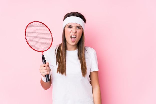 Junge kaukasische frau, die badminton spielt, schreit sehr wütend und aggressiv schreiend.