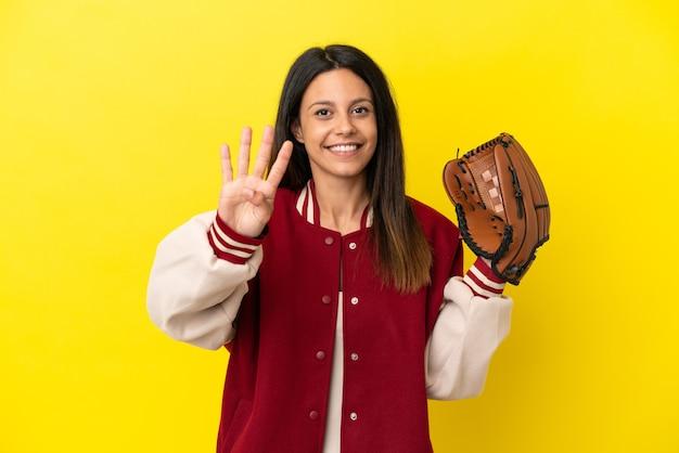 Junge kaukasische frau, die baseball spielt, isoliert auf gelbem hintergrund, glücklich und zählt vier mit den fingern