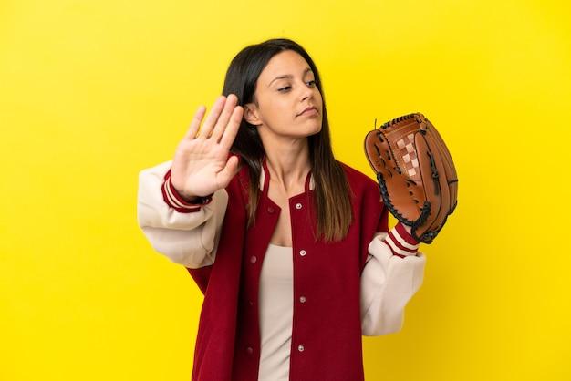 Junge kaukasische frau, die baseball spielt, isoliert auf gelbem hintergrund, macht stop-geste und enttäuscht