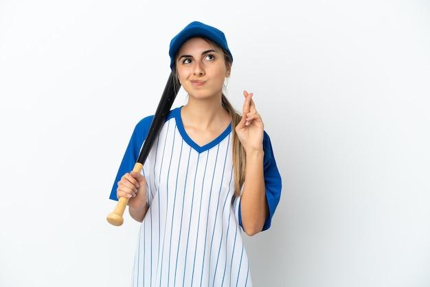 Junge kaukasische frau, die baseball spielt, isoliert mit gekreuzten fingern und wünscht das beste